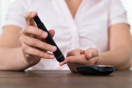 pacientes: Primer plano de manos de mujer Prueba de alta azúcar en la sangre con glucómetro Foto de archivo