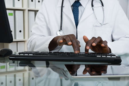 wireless tool: Close-up Of African Male Doctor Typing On Computer Keyboard At Desk