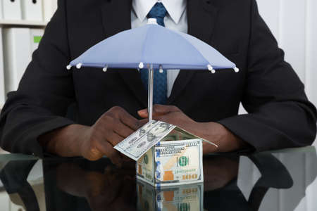 wealth: Close-up Of Businessman Hands Protecting House Of Banknote With Umbrella At Desk