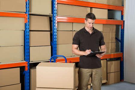 cajas de carton: Trabajador de sexo masculino con cajas de cartón escrito en el portapapeles en almacén Foto de archivo