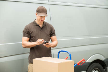 delivery: Young Happy Delivery Man With Cardboard Box Checking List On Mobile Phone