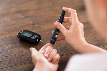 Close-up Of Woman Hands Testing High Blood Sugar With Glucometer