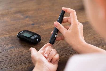 혈당 측정기와 여자 손 테스트 높은 혈당의 근접