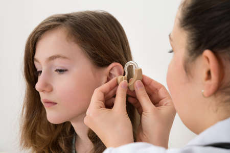 listening ear: Close-up Of Doctor Inserting Hearing Aid In The Ear Of A Girl