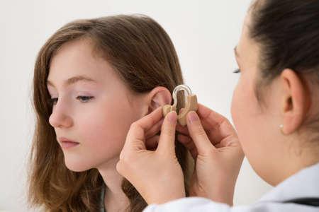 discapacitados: Primer plano de audífono Médico Inserción en el oído de una chica