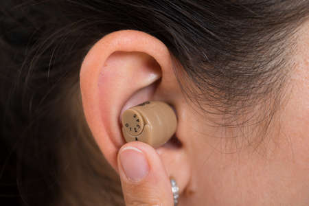 impaired: Close-up Of Woman Ear Wearing Hearing Aid