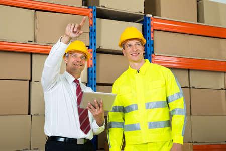inventario: Trabajador del almac�n y gerente de comprobar el inventario en un almac�n grande Foto de archivo