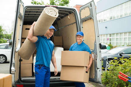 moving box: Two Male Workers Carrying Carpet And Cardboard Boxes In Front Of Van