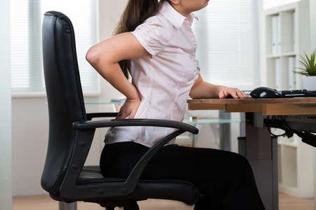 sillon: Primer De La Empresaria Joven En Silla Tener Backpain En Office Foto de archivo