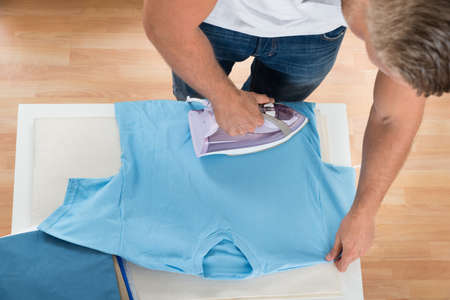 domesticity: Young Man Ironing Clothes With Electric Iron At Home