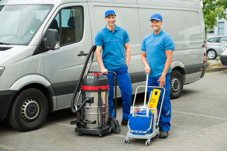 Two Happy Male Cleaners Standing With Cleaning Equipments In Front Van 스톡 콘텐츠