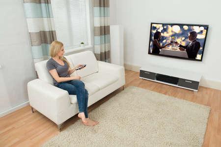 personas viendo television: Mujer joven que se sienta en el sofá viendo la película en la sala de estar Foto de archivo