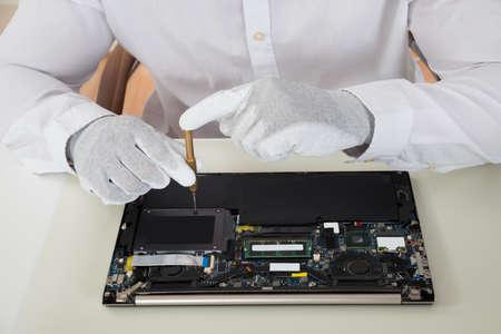 デスクでのノート パソコンの修理技術者のクローズ アップ