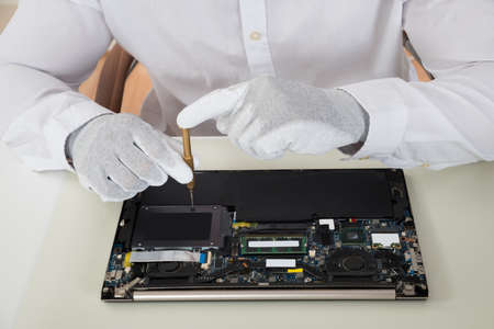 Close-up Of Technician Repairing Laptop At Desk