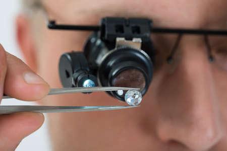 prosperidad: Primer De La Persona Mirando a Diamante Con La Lupa Lupa Foto de archivo