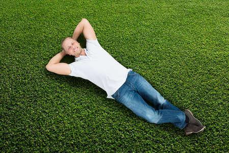 Mladý šťastný muž ležel na zelené trávě
