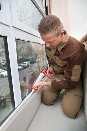 caulking: Young Male Worker Applying Glue With Silicone Gun