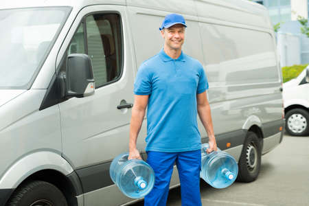man drinking water: Delivery Man With Two Large Water Bottles Standing In Front Of Delivery Van