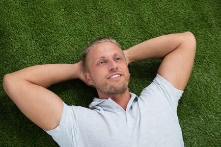 handsome young man: Young Happy Man Lying On Green Grass Stock Photo