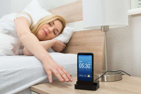 snoozing: Young Woman Snoozing Alarm On Mobile Phone Screen On Nightstand