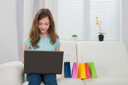 niños de compras: Happy Girl Using Laptop With Small Shopping Bags On White Sofa