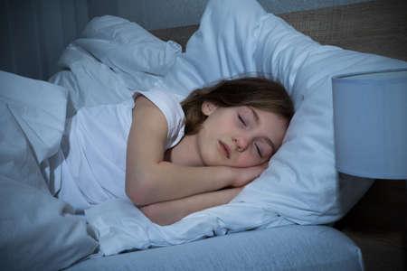 dormir: Linda chica durmiendo en la cama en el dormitorio oscuro Foto de archivo