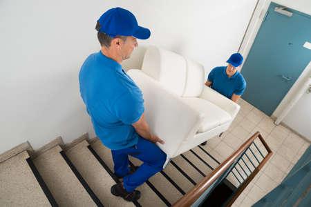High Angle oog van twee Man Movers Dragen Bank Op Trap Van Huis