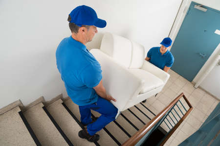 High Angle View Of Two Male Movers Carrying Sofa On Staircase Of House Stock Photo