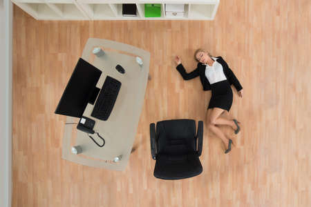 high angles: High Angle View Of Young Businesswoman Fainted On Floor In Office