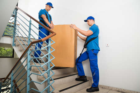 Two Male Movers In Uniform Standing With Box On Staircase Stock Photo