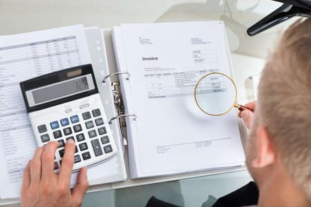 Close-up Of Businessman Inspecting Bills With Magnifying Glass While Using Calculator