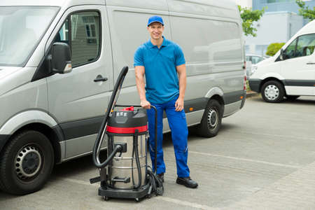 Happy Male Cleaner In Blue Uniform Standing With Vacuum Cleaner
