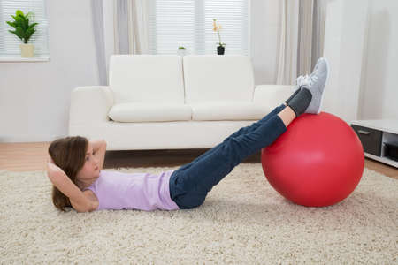 one child: Girl Exercising On Carpet With Red Fitness Ball At Home Stock Photo