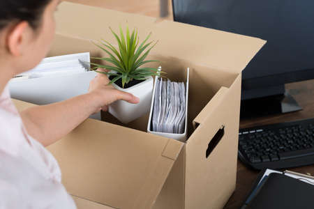 transferred: Young Businesswoman Packing Belongings In Cardboard Box At Desk Stock Photo