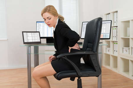 Young Businesswoman Sitting On Chair Suffering From Backache In Office Foto de archivo