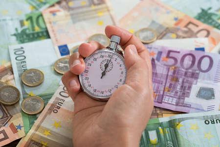 dinero euros: Primer Plano De Fondo persona Manos que sostienen Cronómetro sobre el dinero