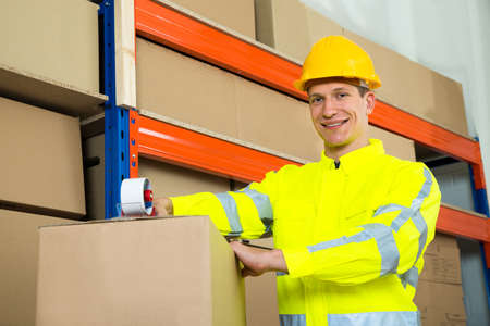 sealing: Male Worker Sealing Cardboard Box With Adhesive Tape In Warehouse Stock Photo