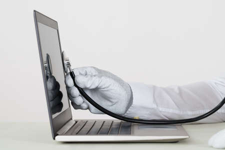 computer devices: Close-up Of Person Hands In White Glove Checking Laptop With Stethoscope Stock Photo
