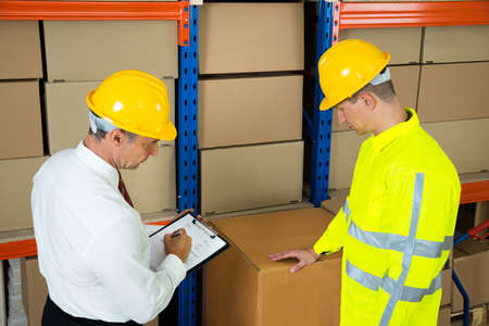 quality work: Manager Holding Clipboard Checking The Inventory With Warehouse Worker