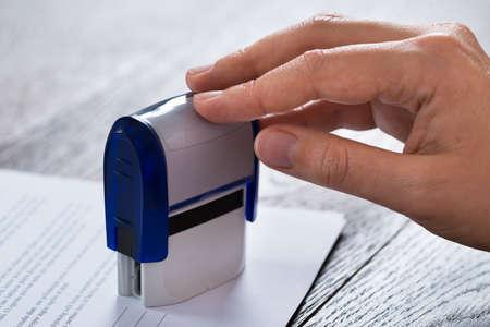 stamper: Close-up Of Person Hands Pressing Stamper On Document