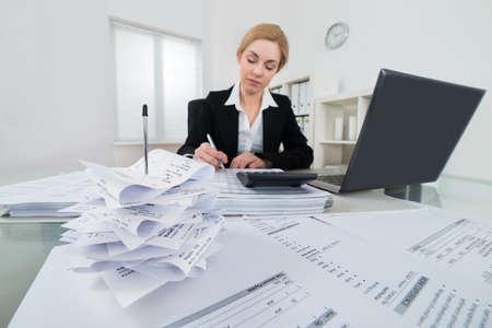 若い実業家の請求書と職場での税金の計算