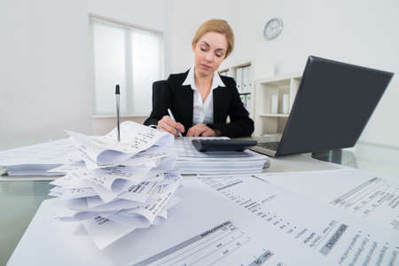 impuestos: Empresaria joven Cálculo de facturas e impuestos en lugar de trabajo Foto de archivo