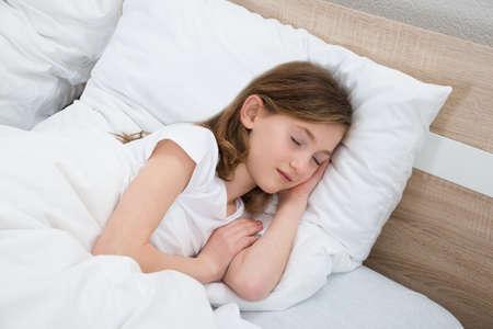 dormir: Linda chica duerme con la manta blanca en cama