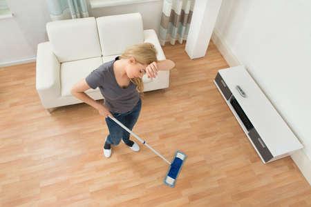 servicio domestico: Opini�n de alto �ngulo Mujer cansada con la fregona en sala de estar Foto de archivo