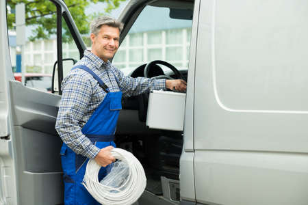 Happy Male Worker With Toolbox And Cable Coil Entering In Van