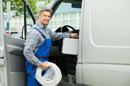 ouvrier: Travailleur heureux Homme Avec bo�te � outils et de c�ble Spirale Saisie Dans Van Banque d'images