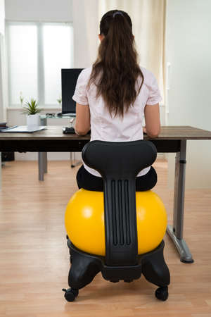 fit ball: Young Businesswoman Sitting On Fitness Ball While Working On Computer In Office
