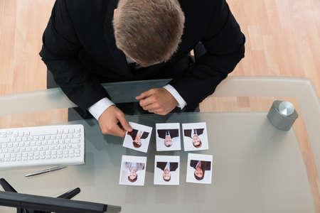 reuniones empresariales: El hombre de negocios joven que mira la fotografía de los candidatos en la Oficina