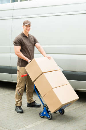 dolly: Young Delivery Man Holding Trolley With Cardboard Boxes