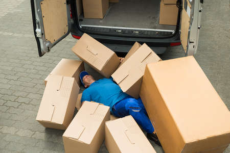 fainted: Unconscious Male Worker Lying On Street Surrounded With Boxes Stock Photo